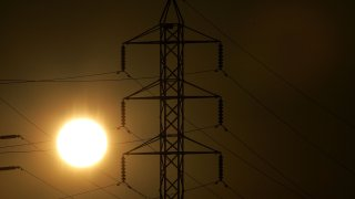 Power towers are seen as the sun sets.