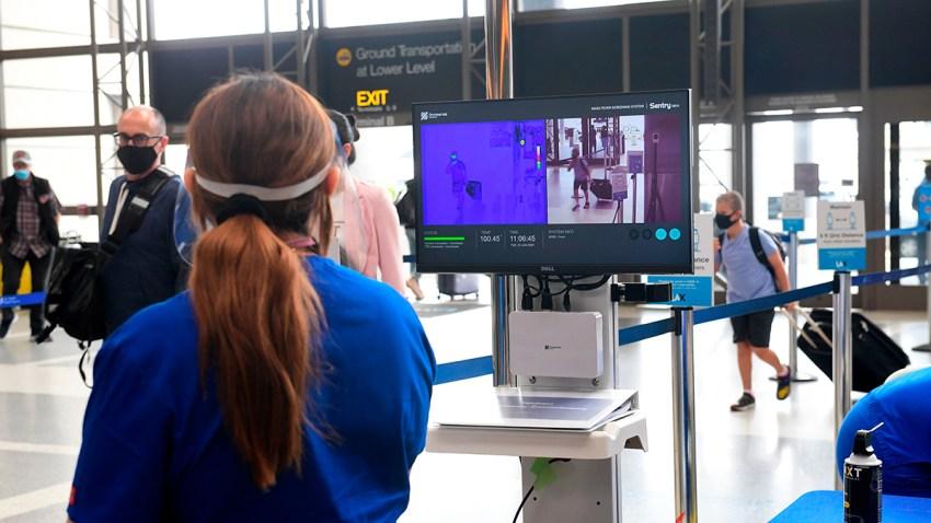 Pasajeros en el Aeropuerto Internacional de Los Ángeles en Los Ángeles caminan frente a cámaras térmicas, este 23 de junio de 2020.