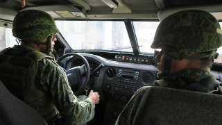 Soldados a bordo de unidad militar.