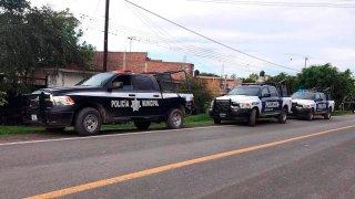 Un grupo de vehículos policiales resguarda el área donde mataron a siete personas