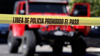 Imagen de un vehículo en medio de una escena de crimen, de la que notifica una cinta amarilla policial